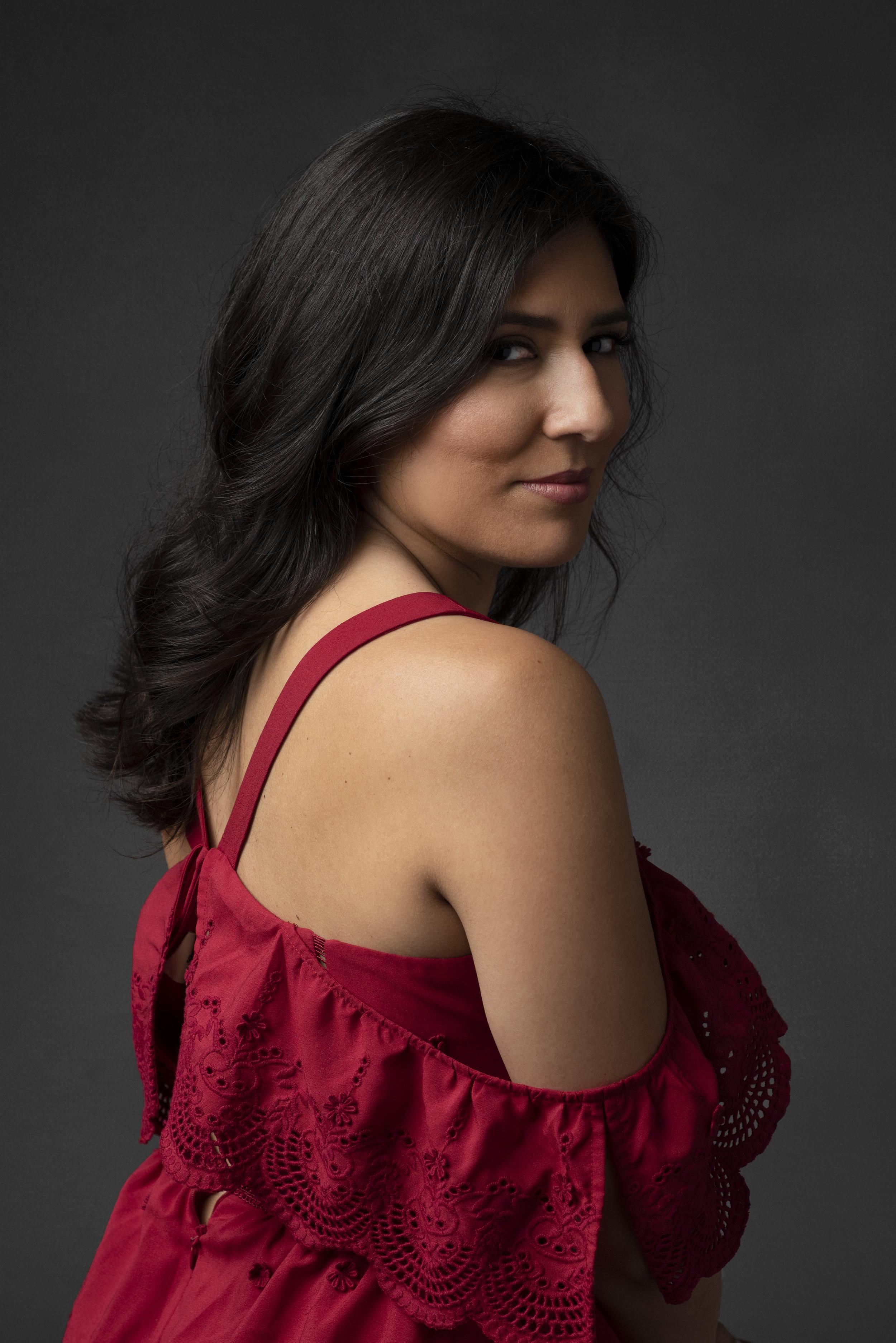 Studio portrait of woman wearing red Spanish style dress.