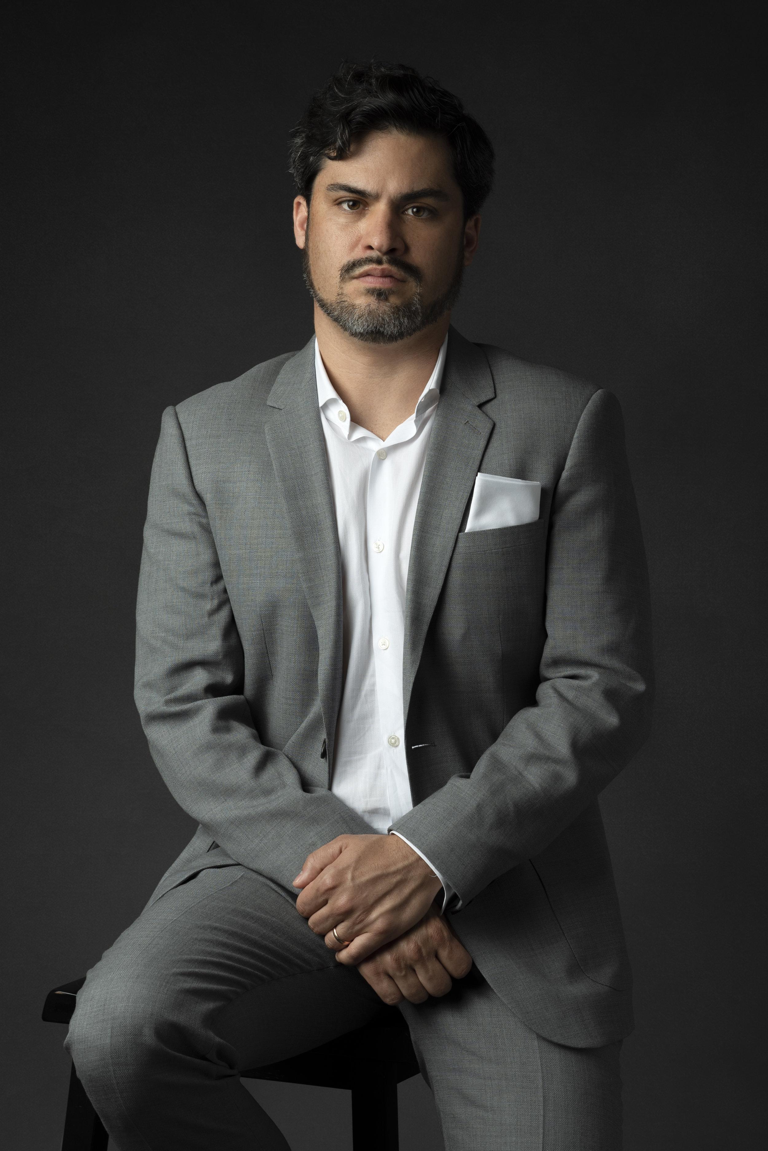 Studio portrait of man in gray suit on gray background