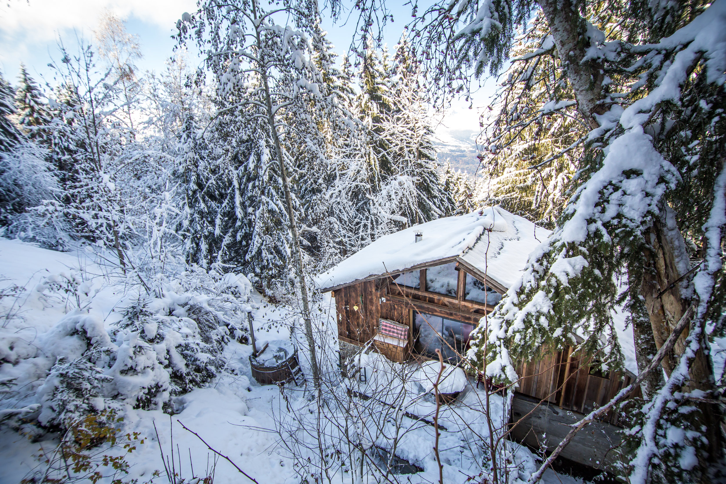 Chalet F'Net at the wood-fired hot tub from above in early winter snow