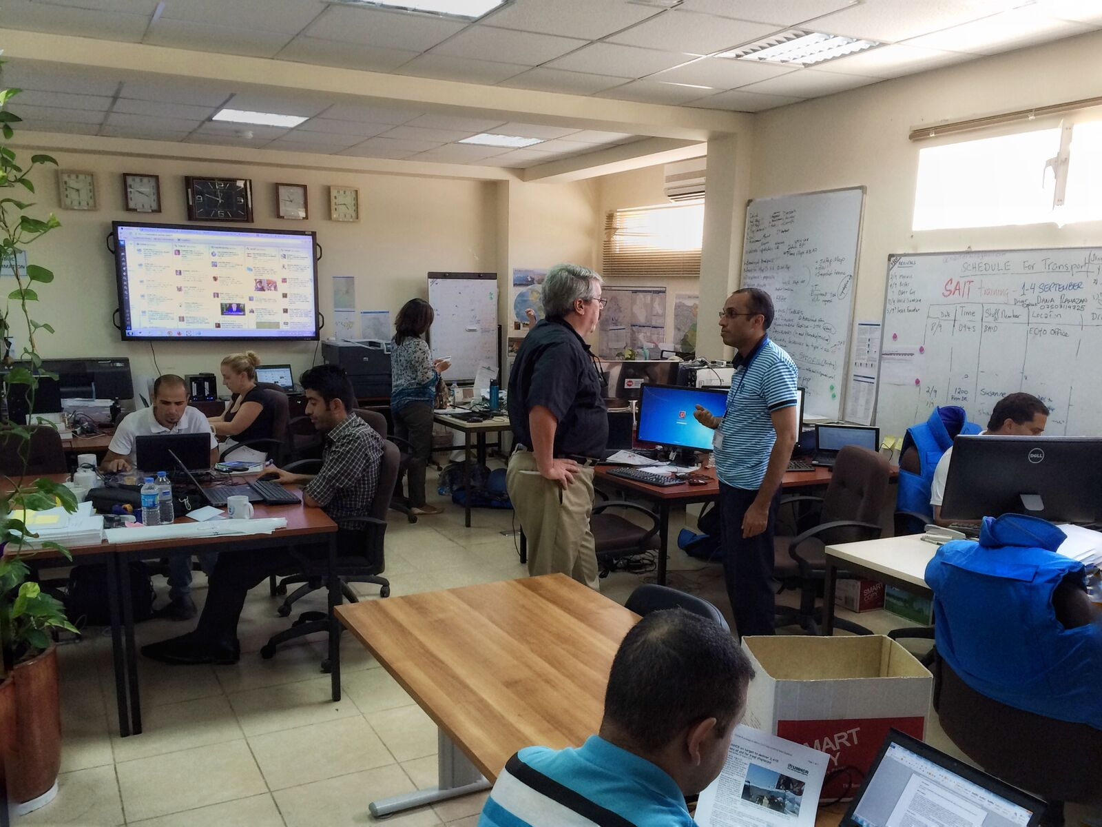 OCHA Iraq Country Office, Erbil, 2014. TweetDeck, for monitoring social media, is on the television in the background. © Brendan McDonald