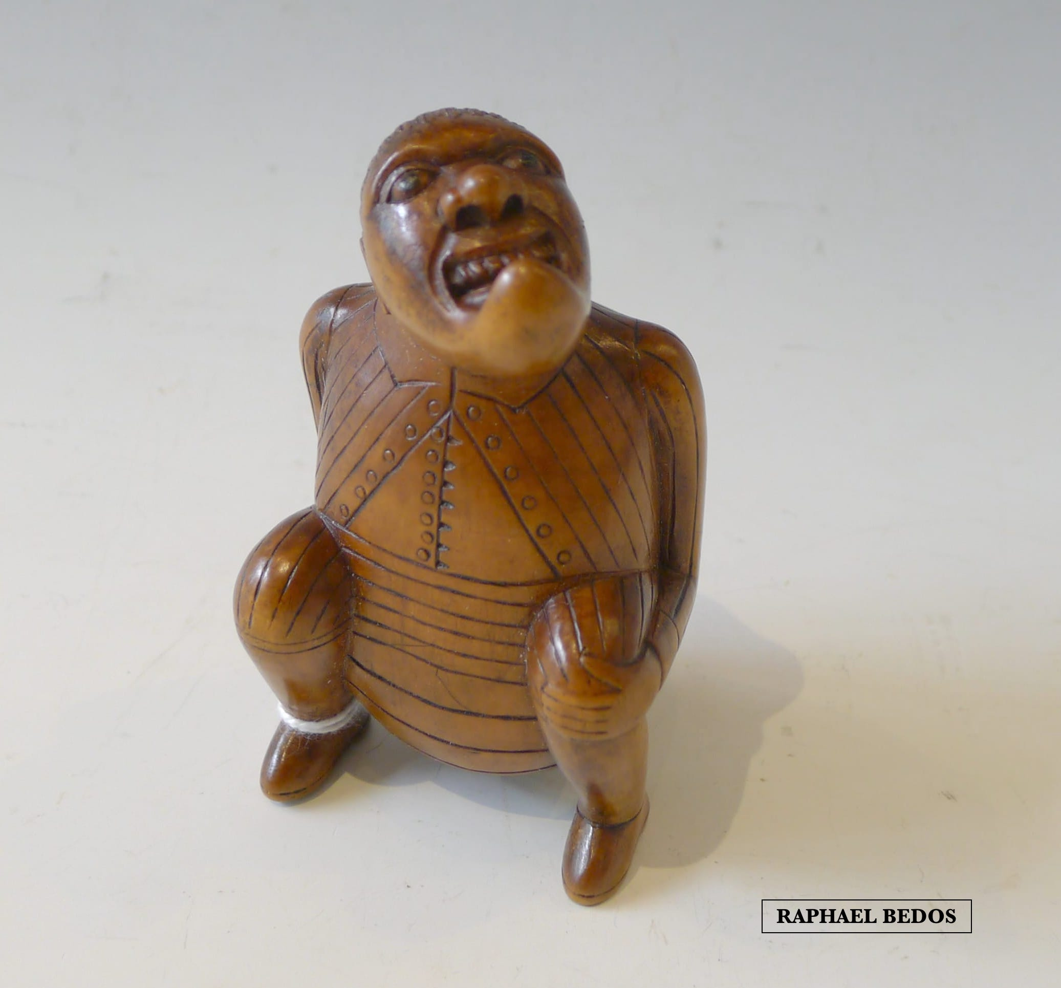 3.Tabatière secouette, personnage accroupi à tête simiesque.Buis.19ème.H:9cm