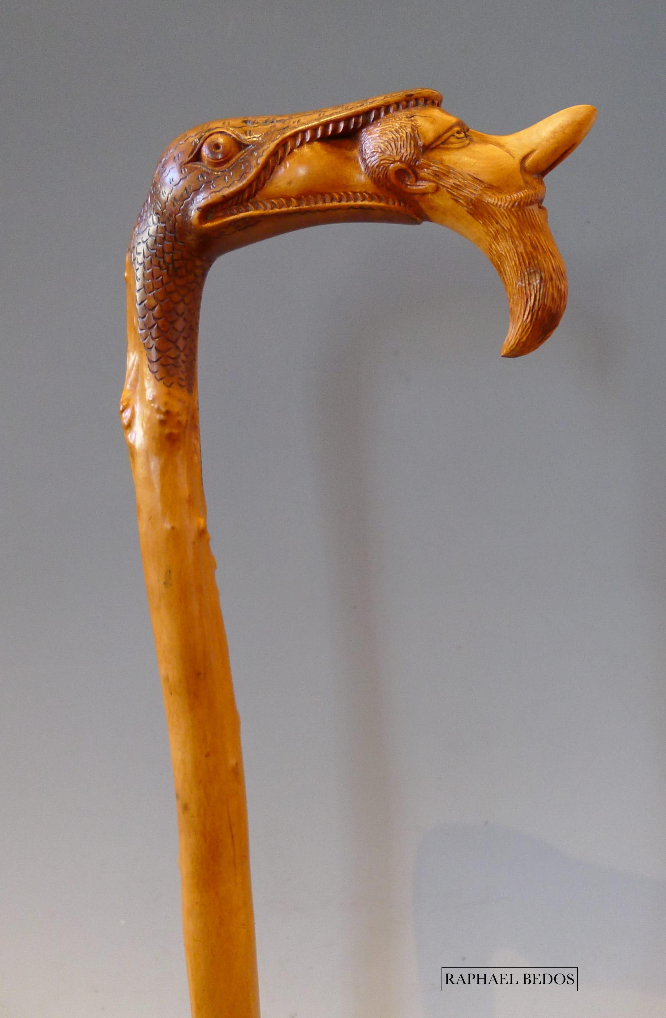 4.Canne à pommeau sculpté d'une tête de reptile tenant dans sa gueule la tête de Cyrano de Bergerac.Buis.19ème.