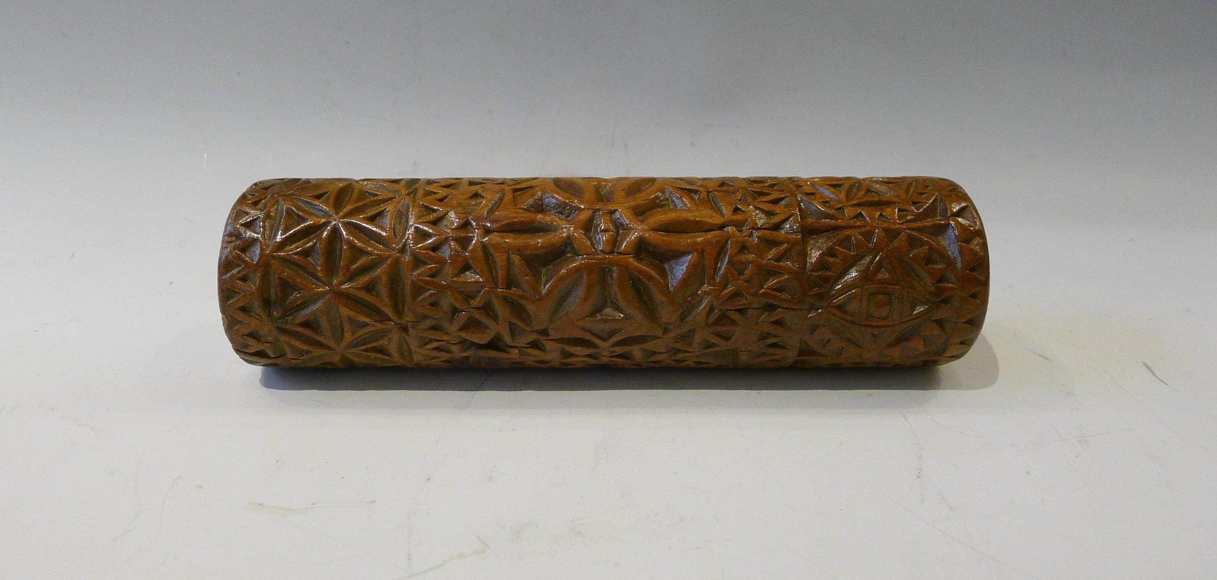 2.Rouleau sculpté en creux d'une rosace centrale à 6 pétales, et de nombreuses rosaces au niveau des bordures, de festons, et de dents de loup, 2 arbres de vie en dessous des 2 rosaces formant un coeur, Queyras, 19ème. L: 19cm