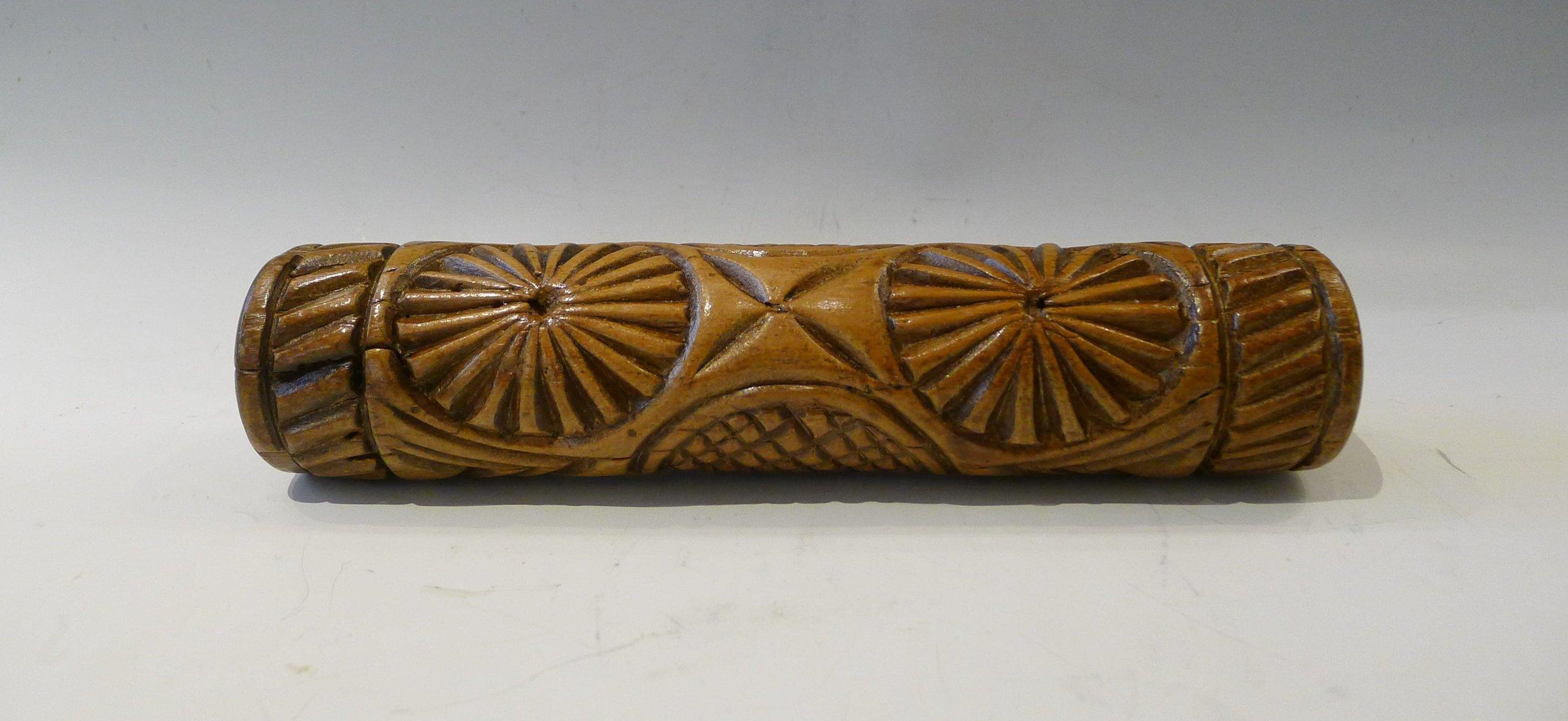 3.Rouleau sculpté en creux de 2 rouelles à multiples branches séparées de 4 pétales en X , garni d'un quadrillage de pointes de diamants arasées.Fente.Auvergne, 19 ème, L: 25 cm.