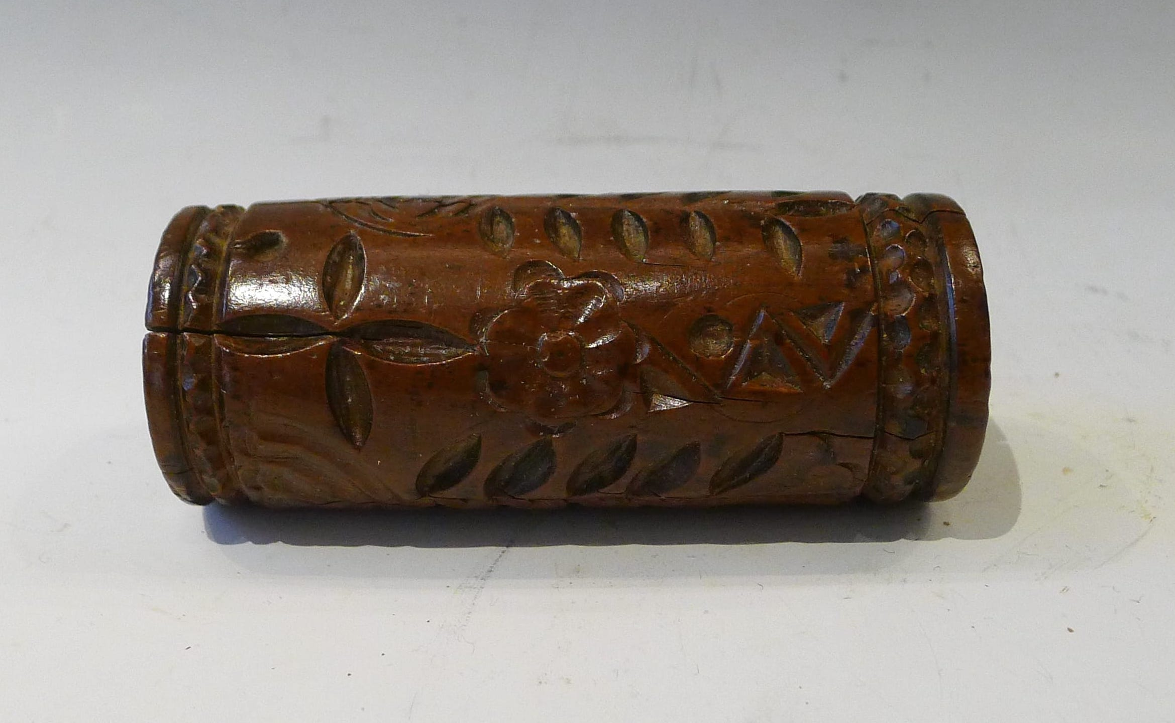 9.Rouleau sculpté en creux d'un arbre de vie, ainsi que 2 fleurs, 2 rameaux, une rosace à 4 pétales, un ostensoir surmonté d'une croix.Bordures chevronnées en relief, légère fente, Normandie, aulne, 18eme. L : 10,5 cm.