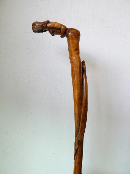 16/Canne au pommeau représentant une femme monoxyle nue, pliée en 2 e un serpent remontant le long du fût.