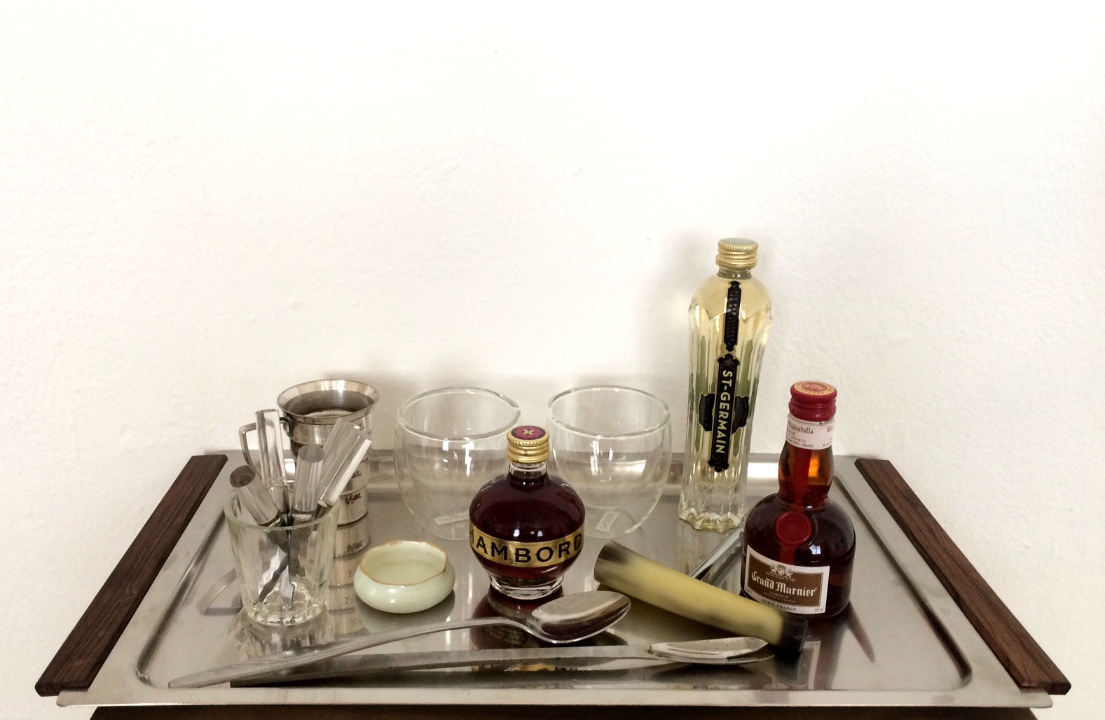"#22: Midcentury stainless tray with rosewood handles (Denmark), Bodum espresso cups, sterling measuring cup, acrylic and silver hors d'oeuvres forks, enamel salt cellar (Vienna), and bone-handled corkscrew. 3"" x 15"" x 8.5"" (SOLD)"