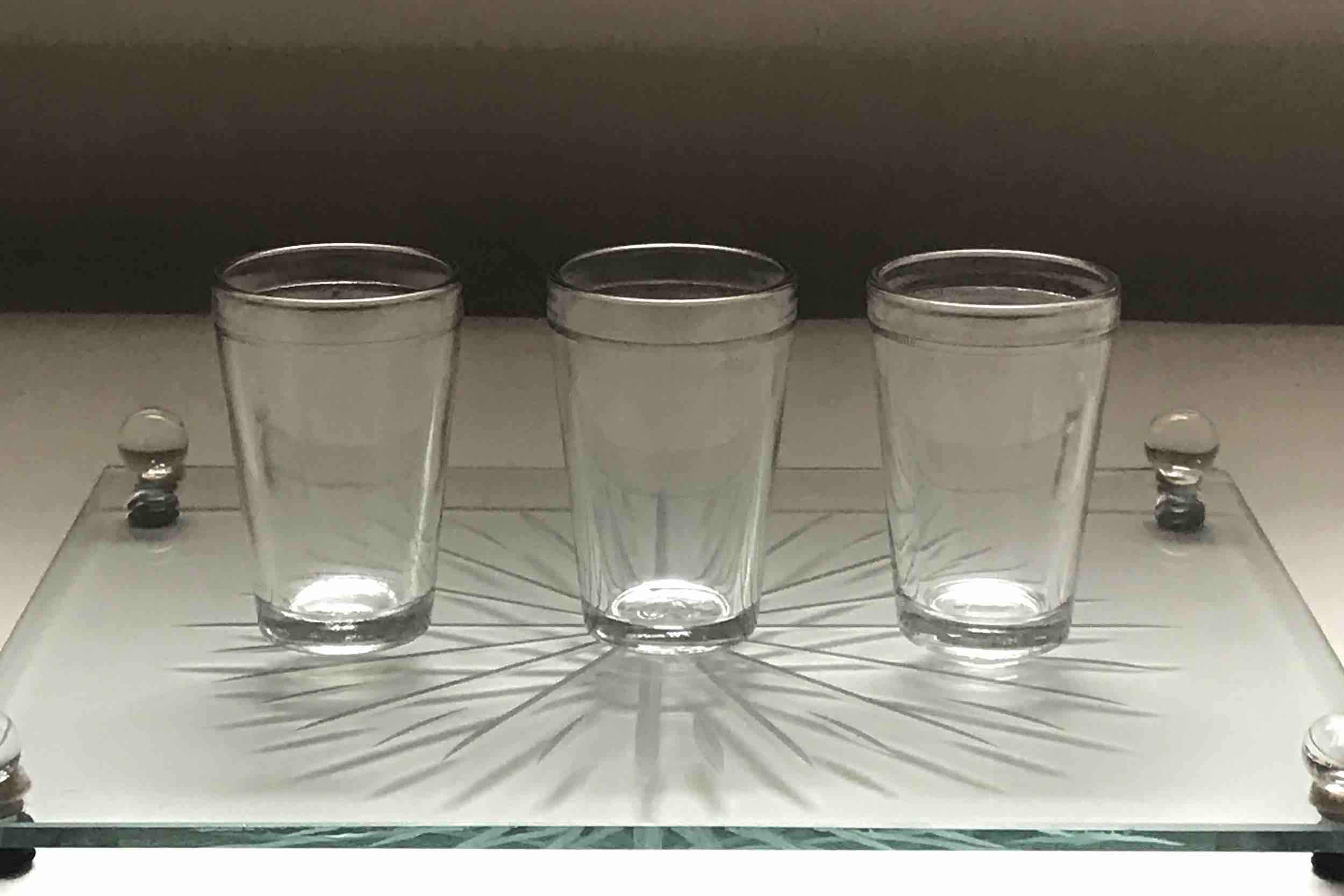 "#26: Three juice glasses on platform etched with sunburst pattern. 3"" x 10""x 8"""
