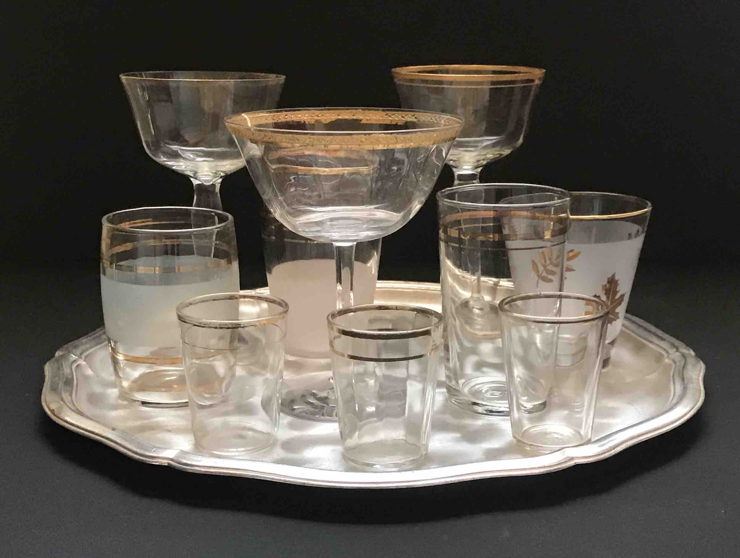 #9: Set of ten gold-trimmed glasses (3 stems, 4 tumblers, 3 shot glasses) on brushed silver platter.
