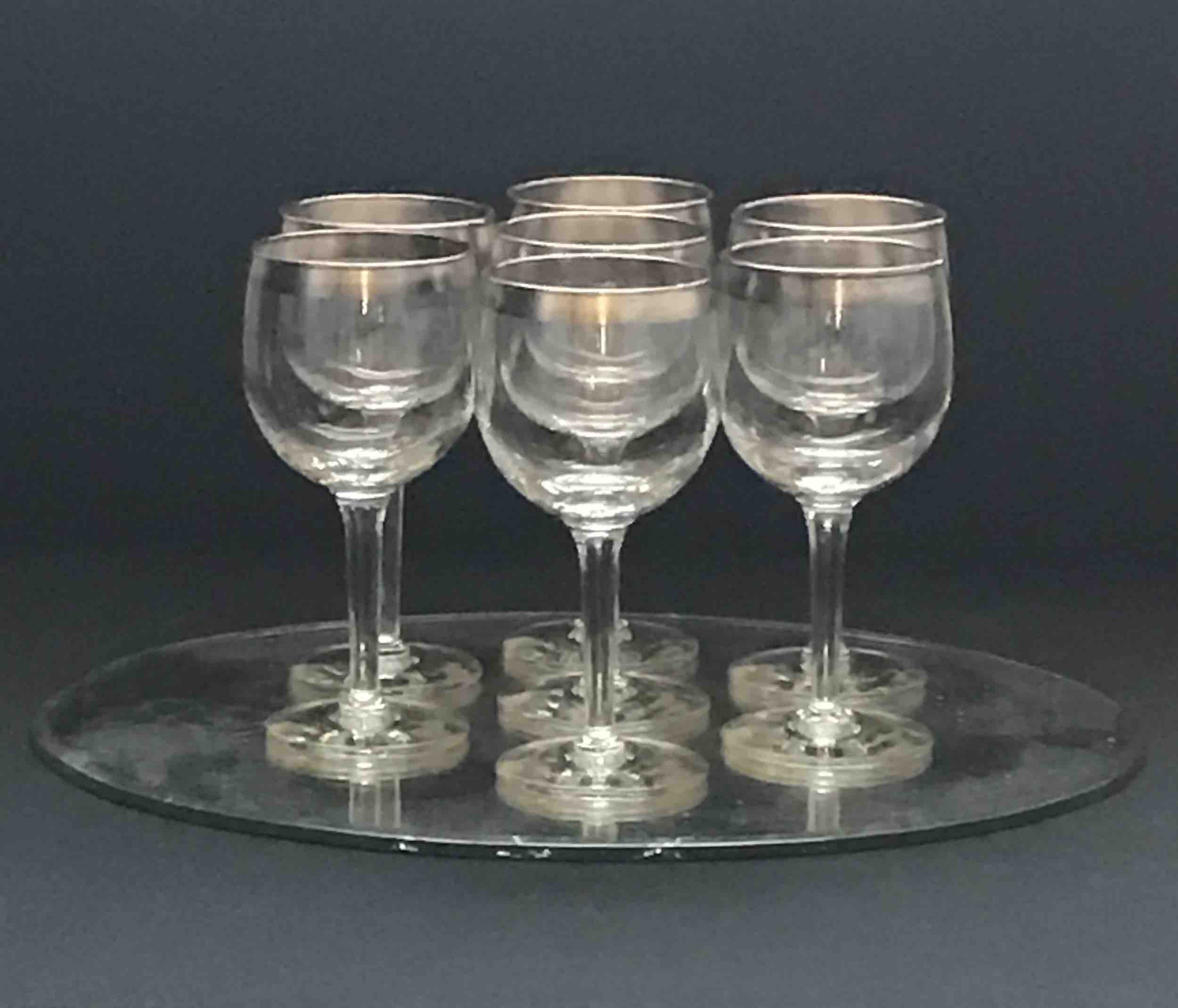 "#10: Seven silver-rimmed Dorothy Thorpe wineglasses on oval, silvered Mercury glass mirror. 6.5"" x 11"" x 9"""