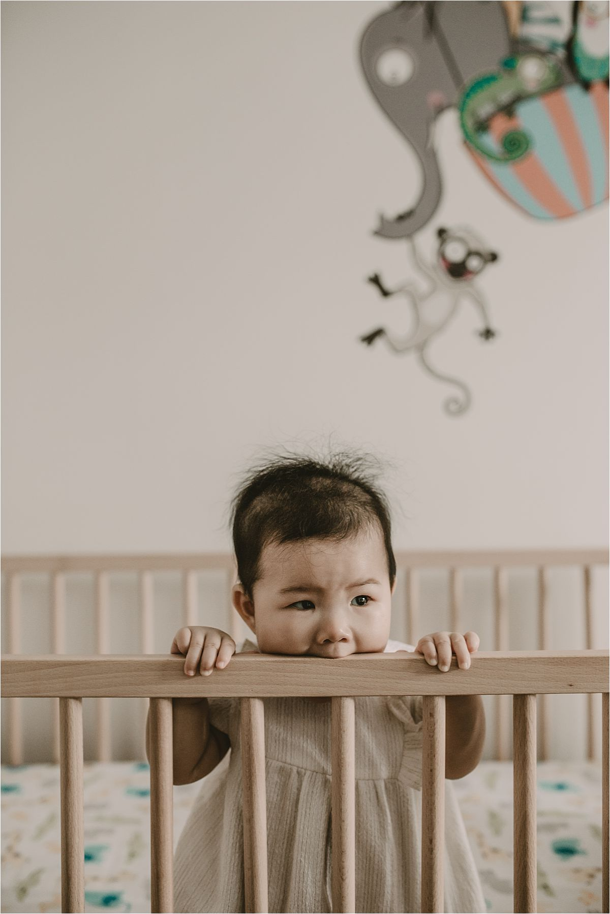 nyc family and newborn photographer baby girl peeks over crib rails in Queens home