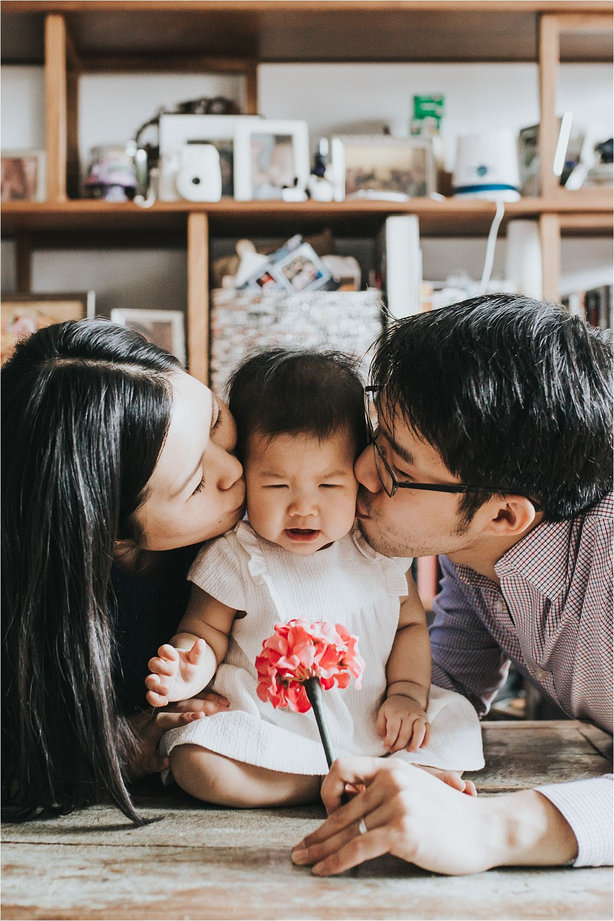 nyc family and newborn photographer mom and dad kiss baby girl's cheeks