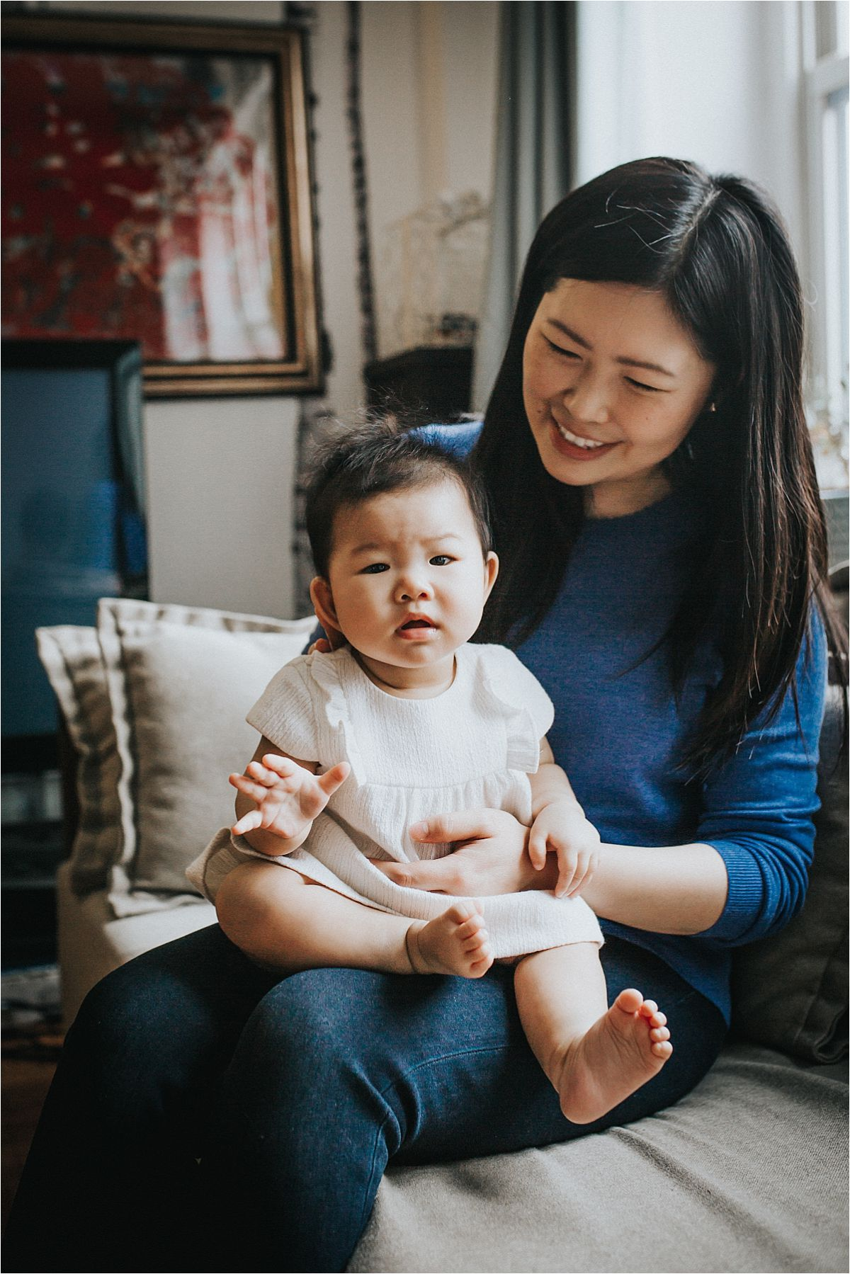 nyc family and newborn photographer baby girl sits on mom's lap in sun filled living room