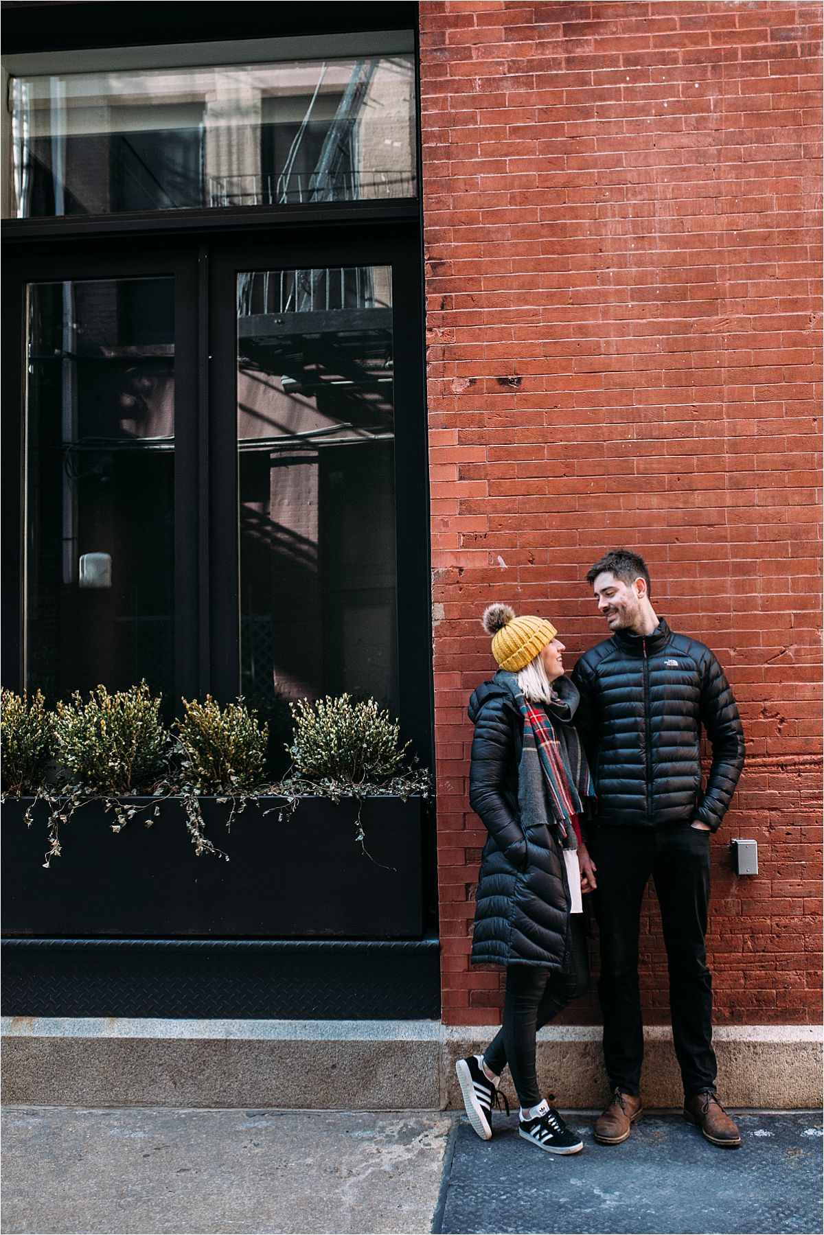 nyc newborn and family photographer married couple standing next to window