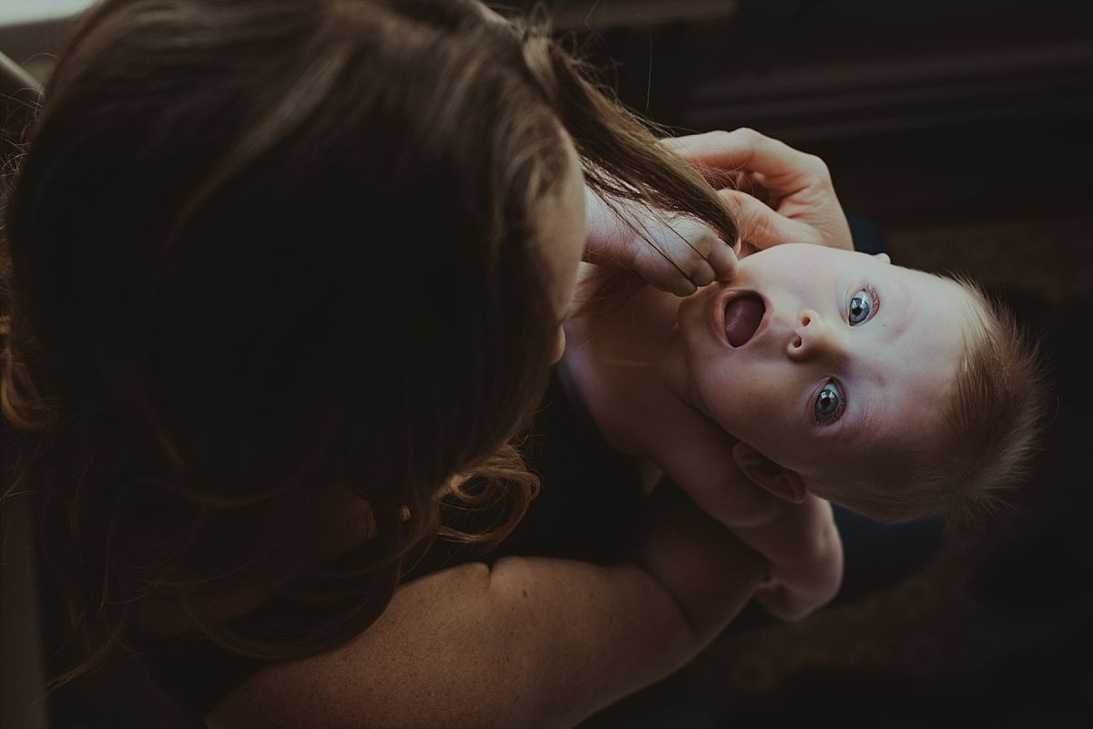 nyc newborn and family photographer mom and baby playing and baby chewing mom's hair