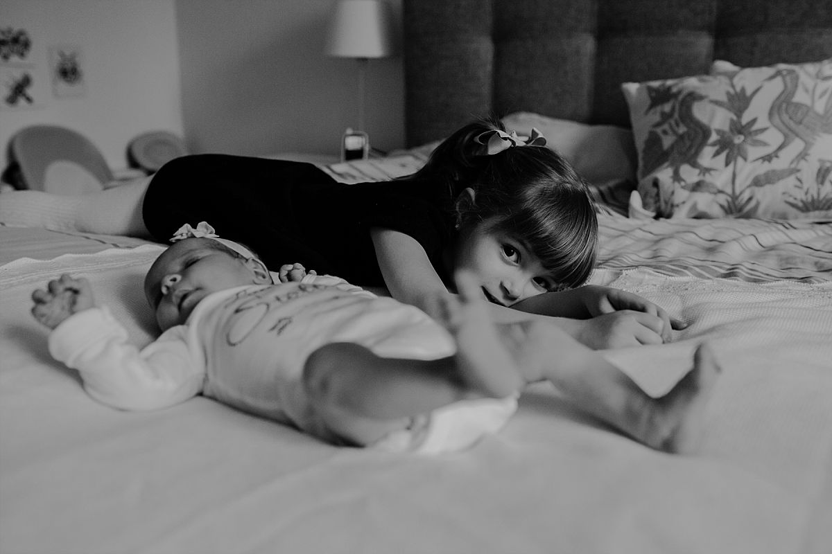 nyc family and newborn photographer big sister lies with newborn sister on bed