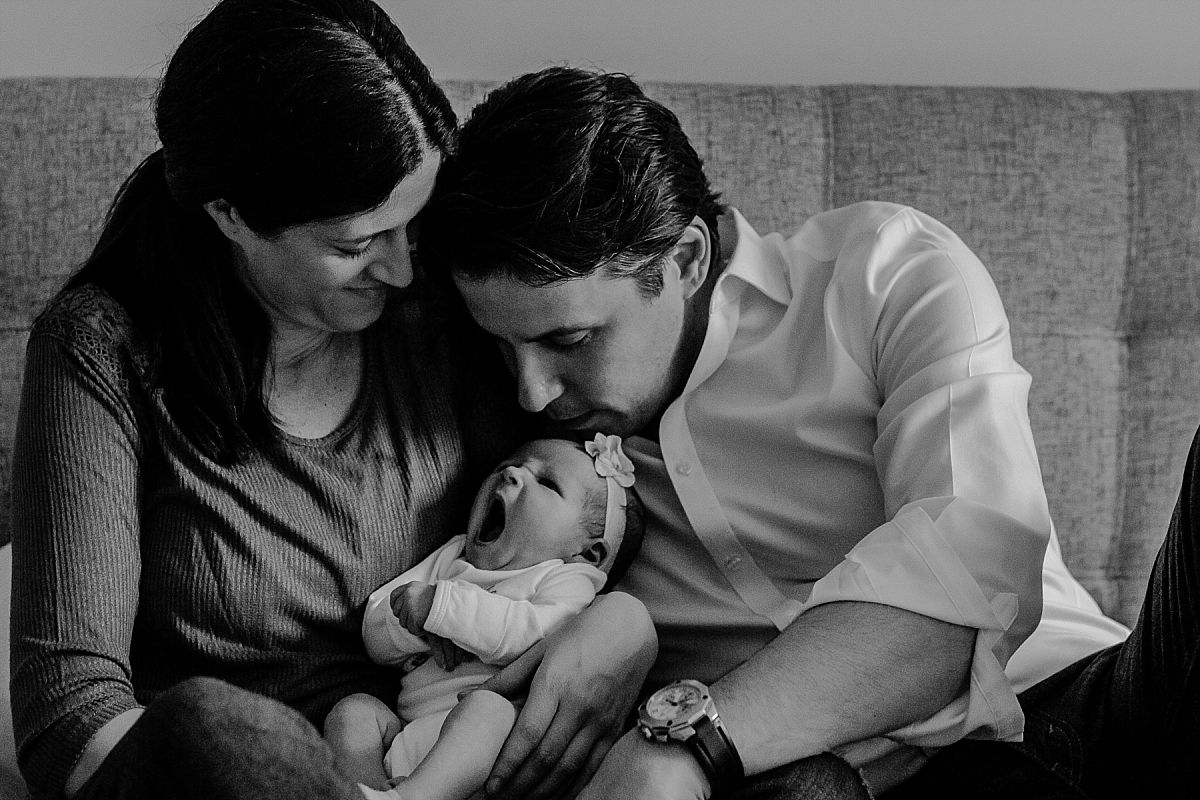 nyc family and newborn photographer mom, dad and newborn on bed with newborn yawning