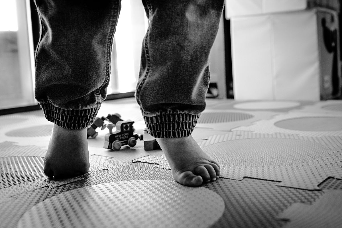 nyc family and newborn photographer toddler boy feet play on colorful mat