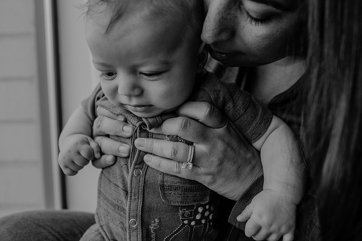 nyc family and newborn photographer mom kisses newborn toddler son near window