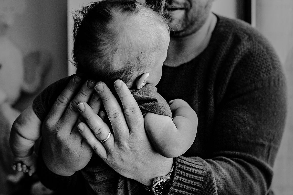 nyc family and newborn photographer dad holds newborn son closeup on window sill