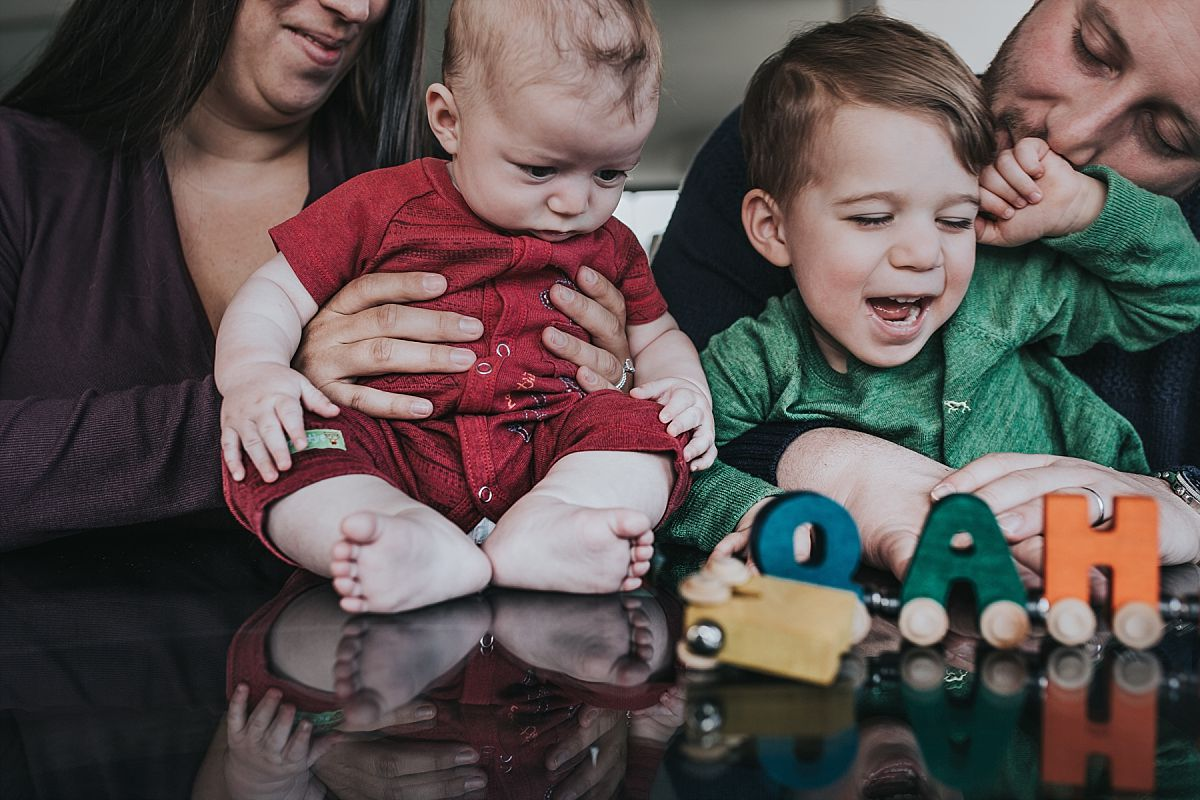 nyc family and newborn photographer family sits at table and plays with wooden name blocks