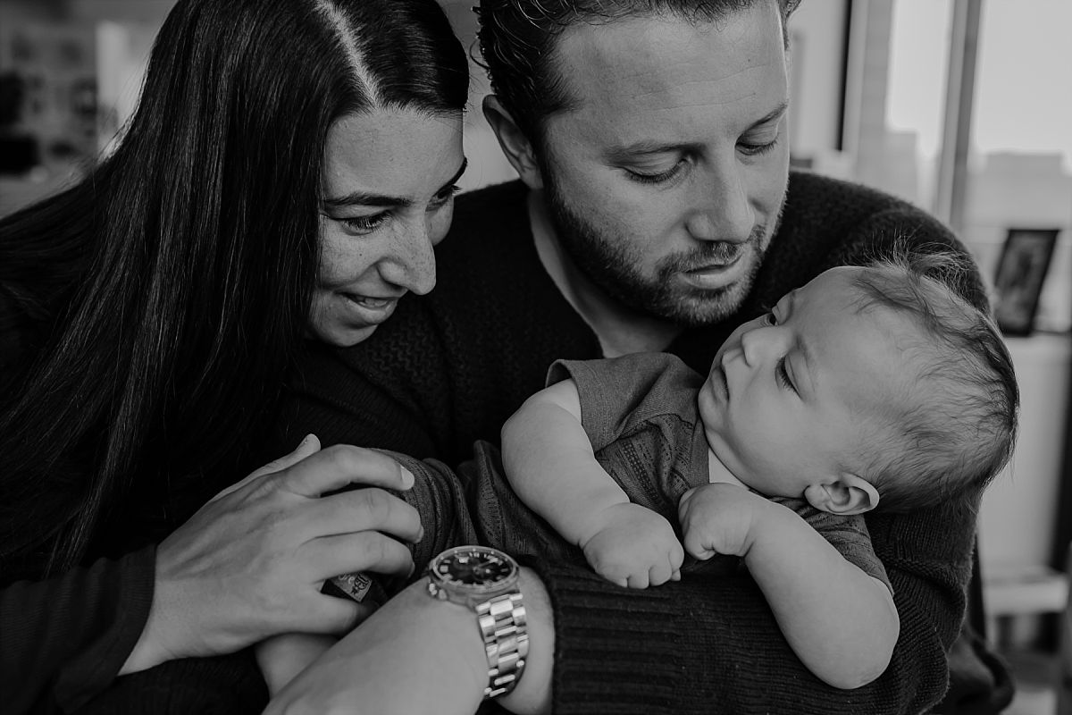 nyc family and newborn photographer mom and dad at kitchen table hold newborn baby boy