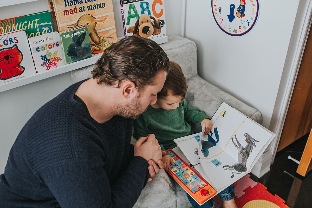 nyc family and newborn photographer dad and toddler boy read together in boy's room