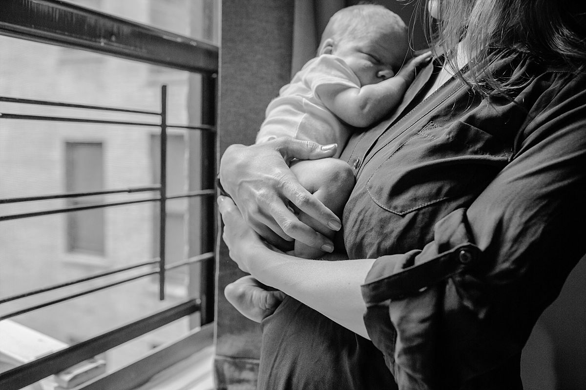 nyc family and newborn photographer Israeli mom holds newborn boy as he cuddles in her arms