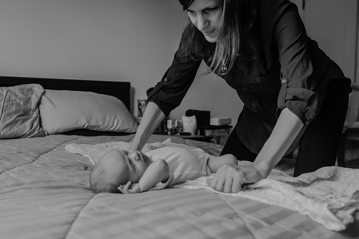 nyc family and newborn photographer Israeli mom lies newborn boy on bed and looks lovingly at him