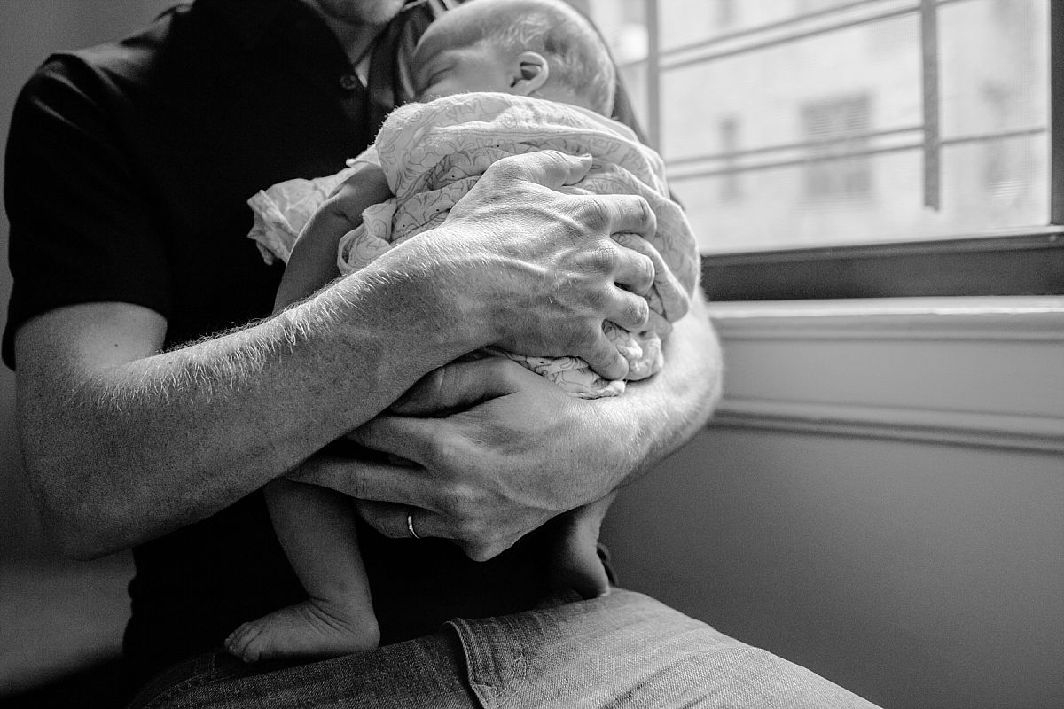 nyc family and newborn photographer dad holds newborn son in living room of Park Slope apartment