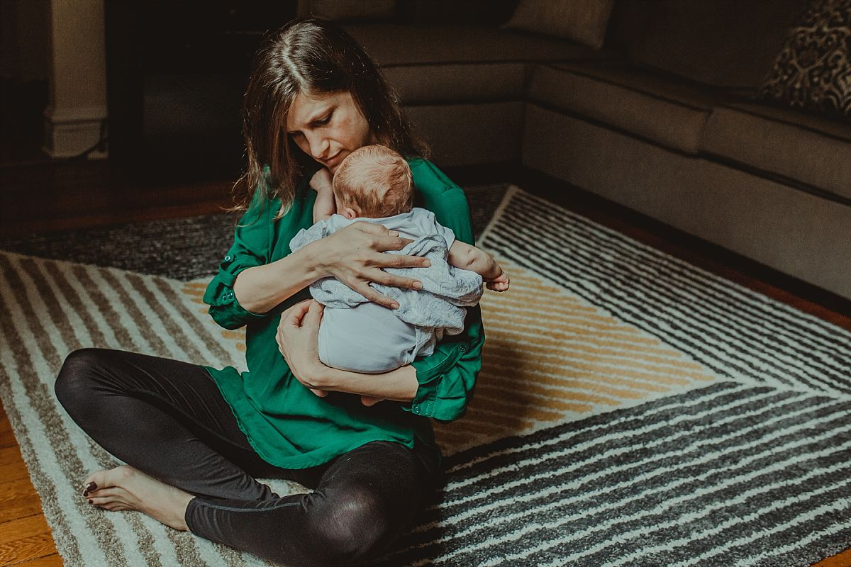 nyc family and newborn photographer mom holds newborn son on shoulder on rug in living room of Park Slope abode