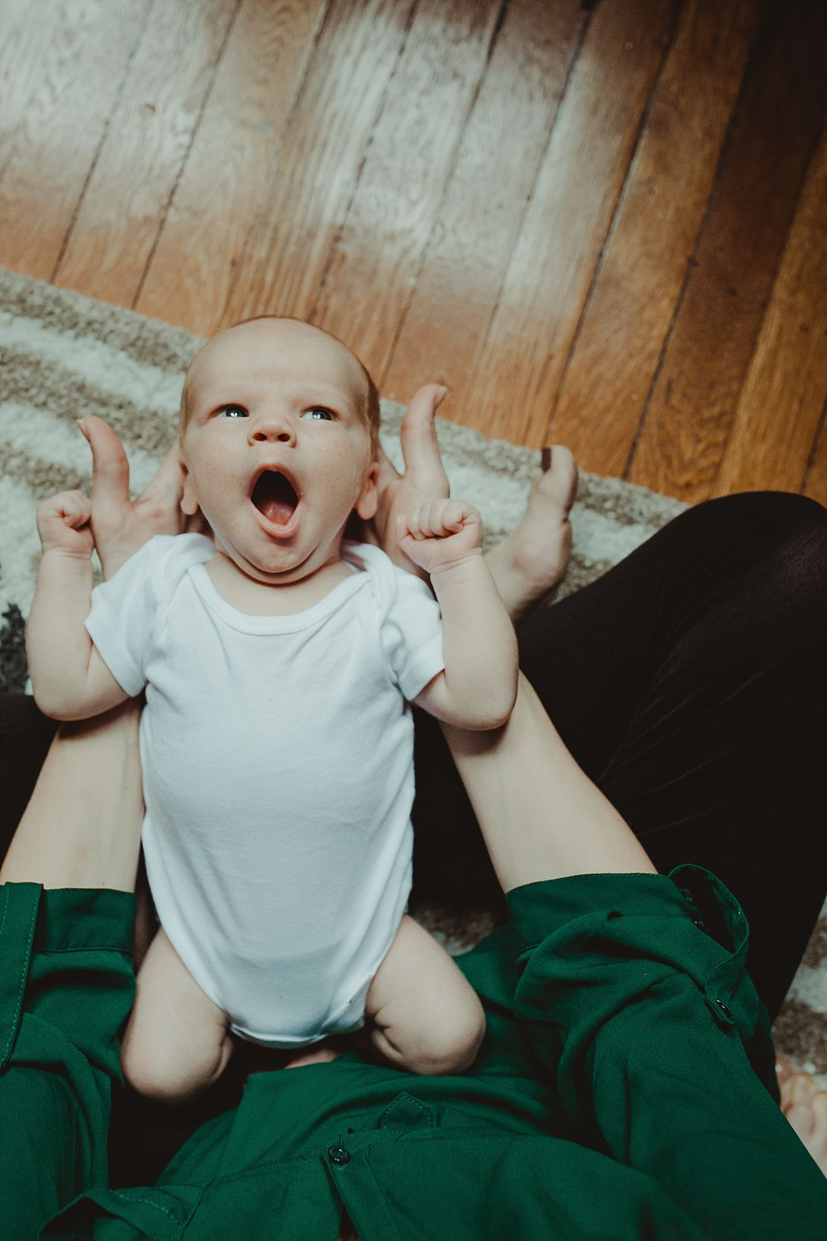 nyc family and newborn photographer mom holds yawning newborn son sitting on rug in living room