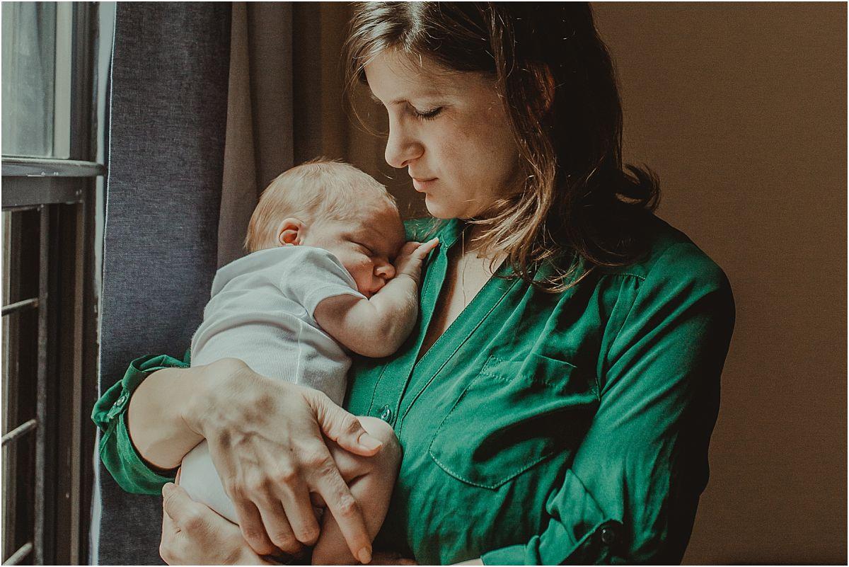nyc family and newborn photographer mom holds sleepy newborn son near light filled window