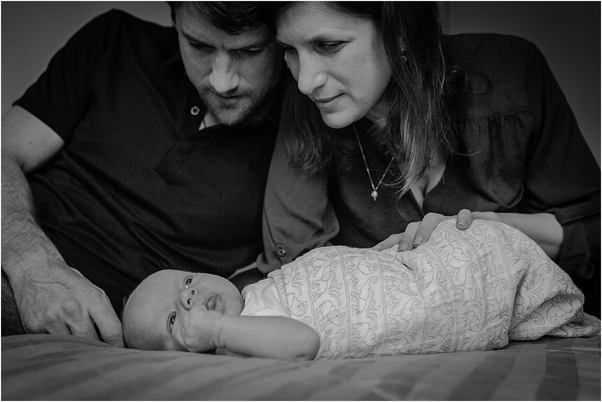 nyc family and newborn photographer mom and dad peer at newborn son while sitting on bed