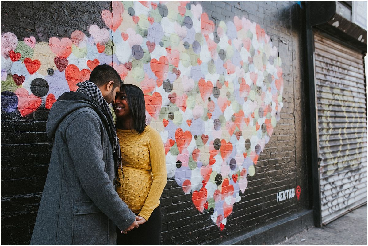 nyc family and newborn photographer expecting mom and dad sit holds hands in front of East Village graffiti wall