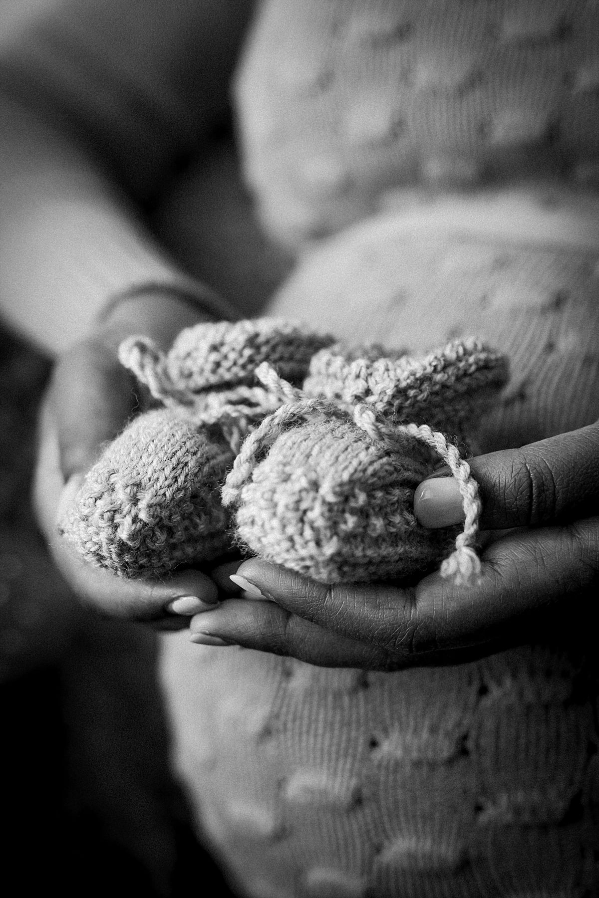 nyc family and newborn photographer expecting mom holds newborn hand sewn baby boots at home