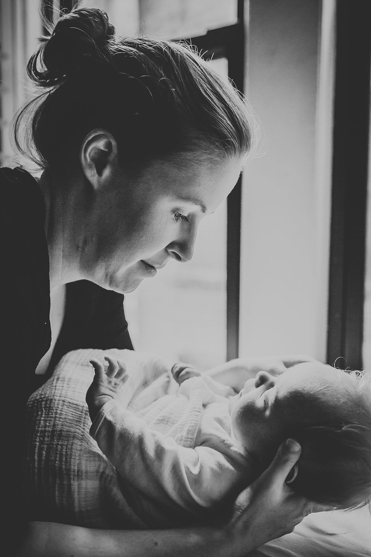 nyc family and newborn photographer new mom holds sleeping newborn baby girl in arms of Chelsea home