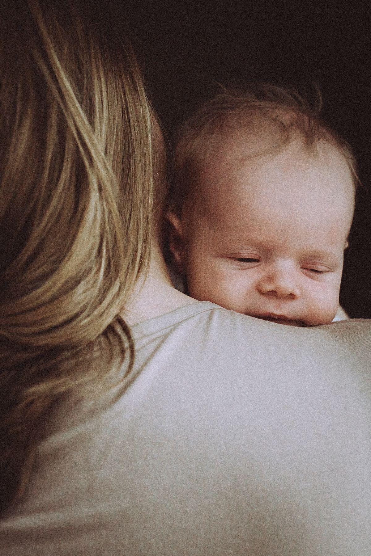 nyc family and newborn photographer newborn baby girl pokes head over mom's shoulder
