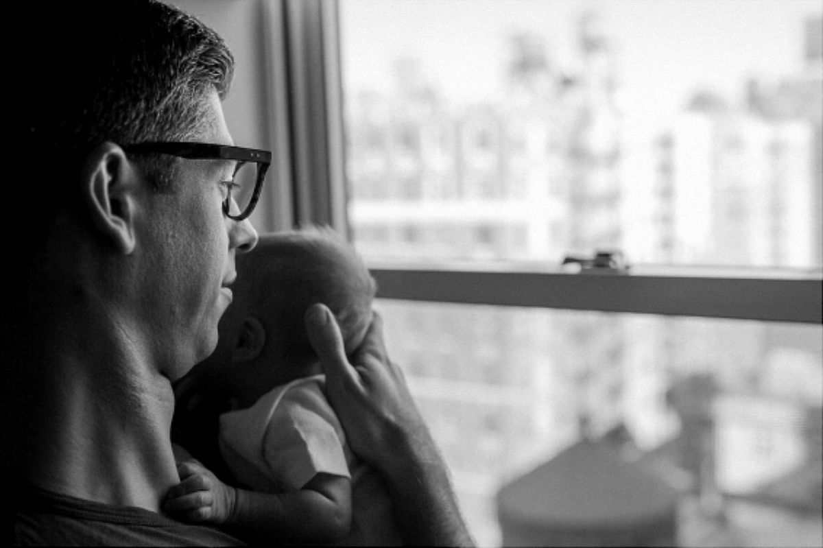 nyc family and newborn photographer dad holds newborn son by window of upper west side apartment