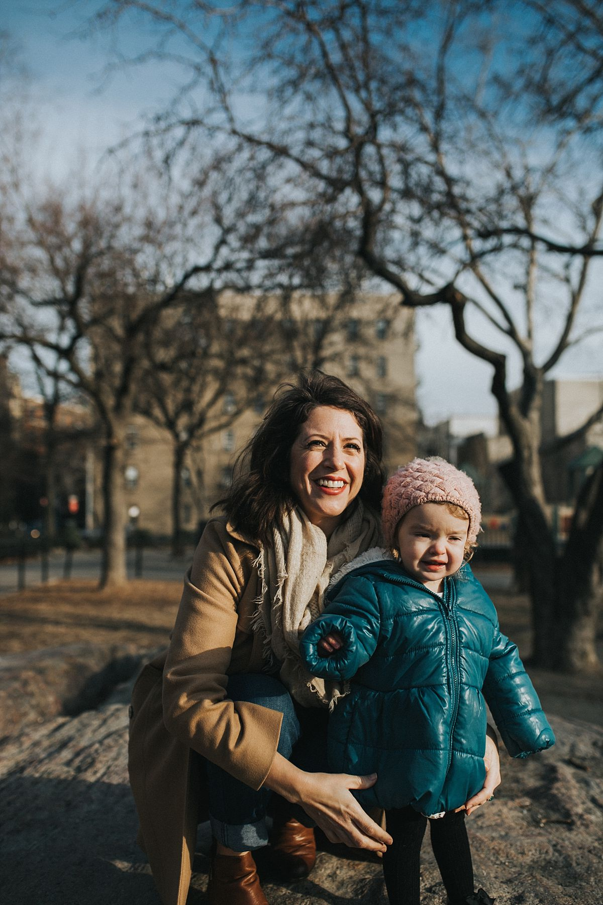 nyc family and newborn photographer mom and toddler daughter on rock in nyc park