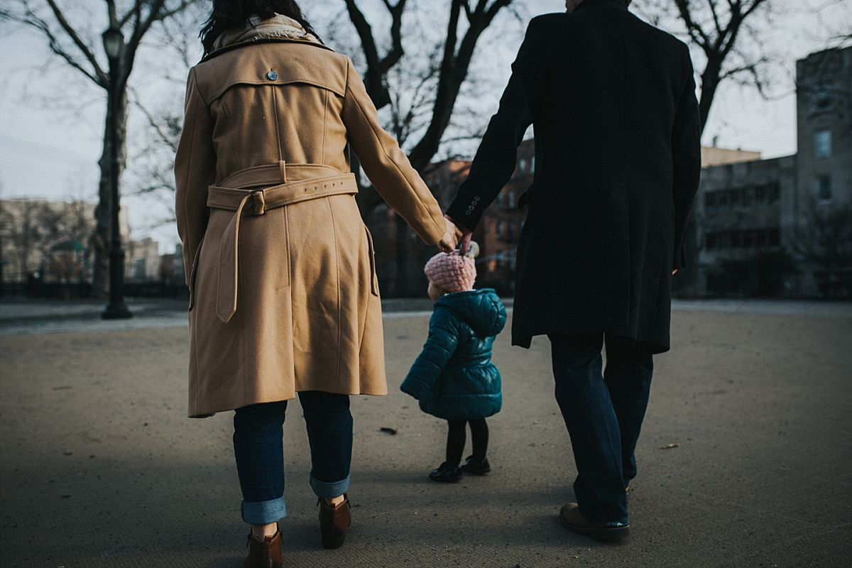 nyc family and newborn photographer mom and dad hold hands and toddler daughter walks in front in nyc park