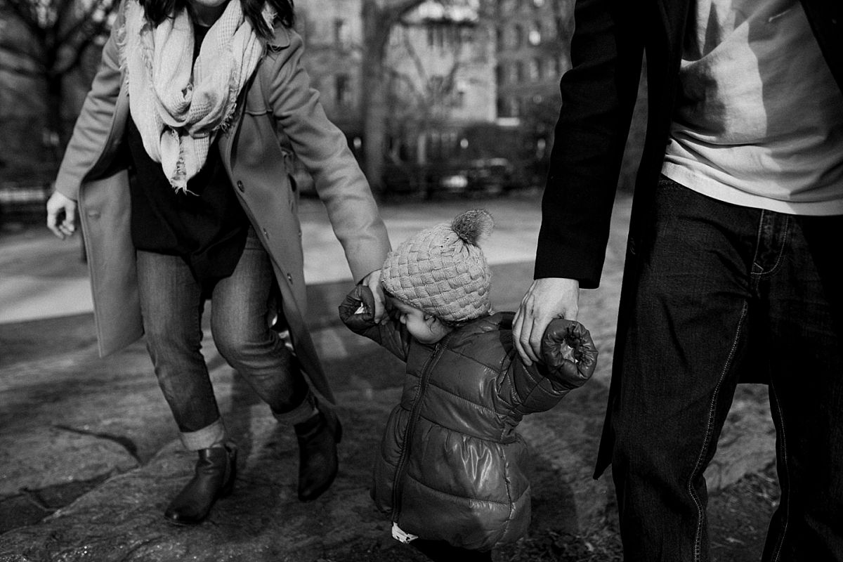 nyc family and newborn photographer mom, dad and daighter hold hands in park