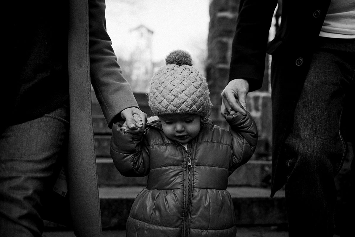 nyc family and newborn photographer mom, dad and daughter hold hands walking down park stairs in nyc