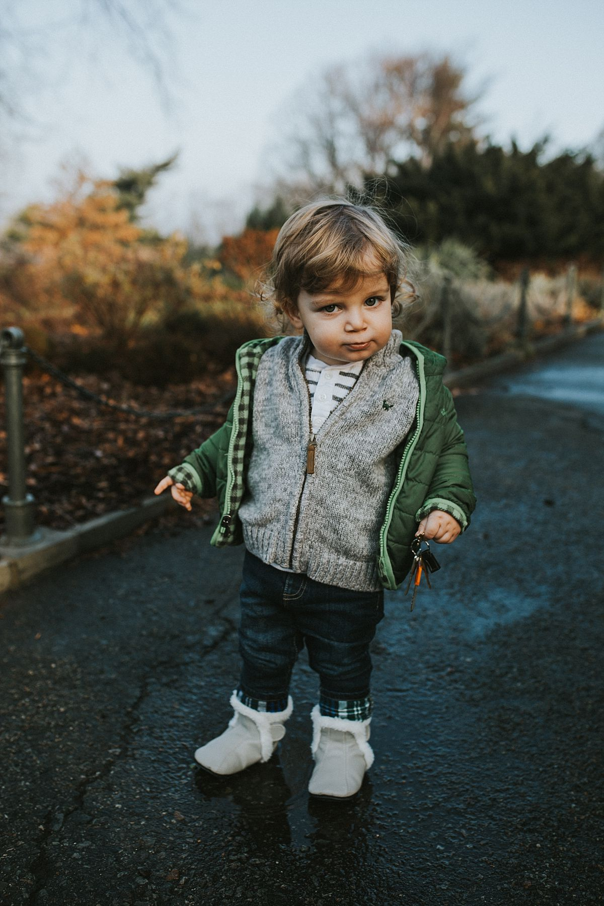 nyc family and newborn photographer toddler pulls silly face standing on path in nyc park