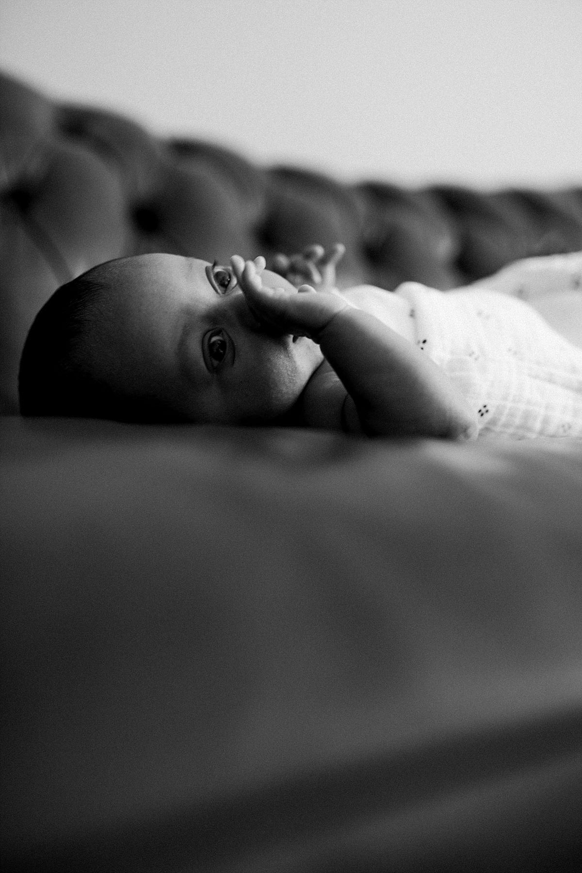 nyc family and newborn photographer newborn girl lies on couch and stetches arms out at in home session