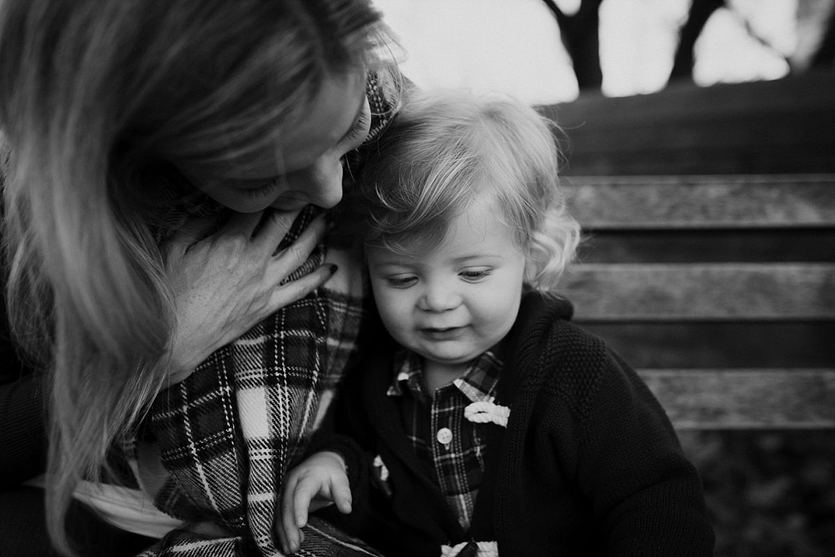 nyc family and newborn photographer mom and toddler boy sitting on nyc park bench for outdoor family lifestyle session image in black and white