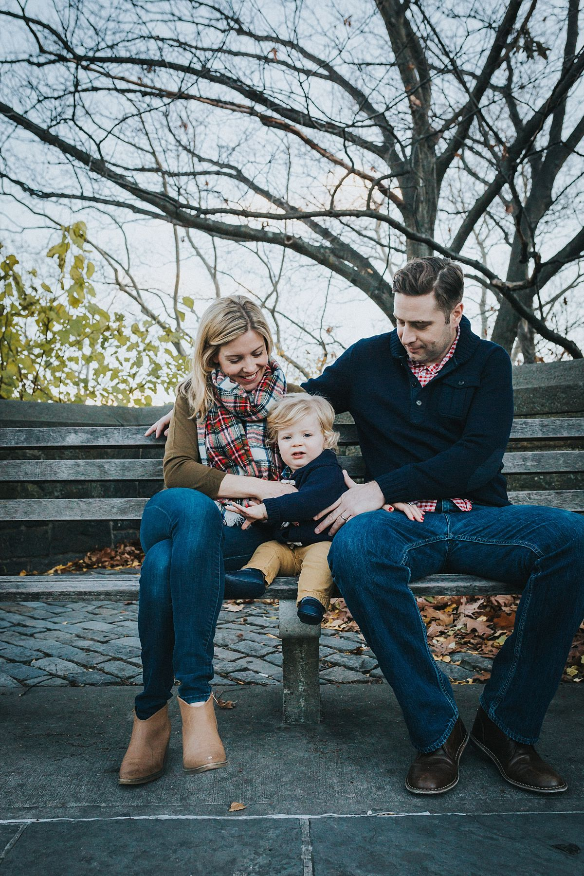 nyc family and newborn photographer mom, dad and toddler boy sitting on nyc park bench for outdoor family lifestyle session