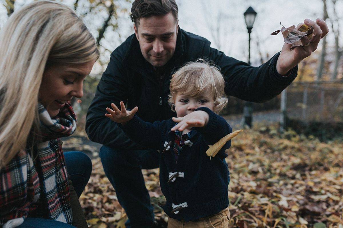 nyc family and newborn photographer mom, dad and toddler boy play amongst fall leaves in nyc park for family lifestyle session