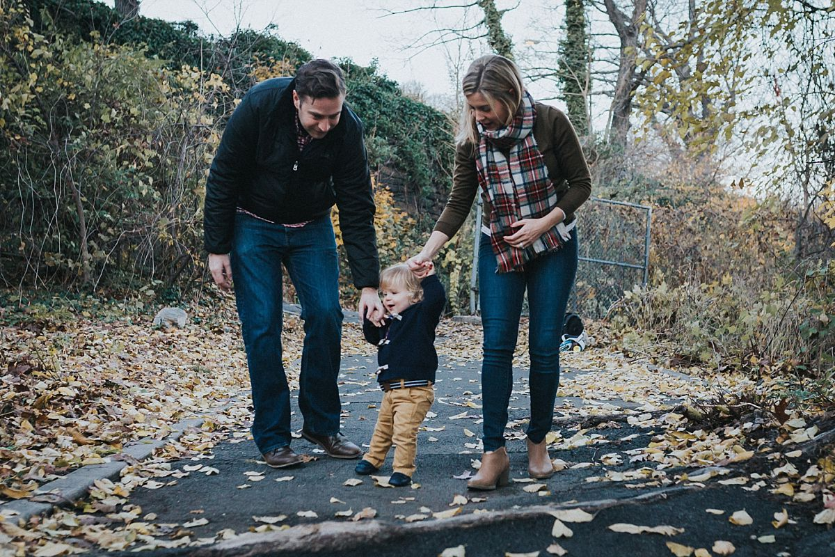 nyc family and newborn photographer mom, dad and toddler boy walk amongst fall leaves in nyc park for family lifestyle session