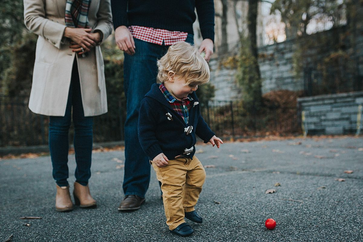 nyc family and newborn photographer mom, dad and toddler boy play in nyc park while toddler chases red ball